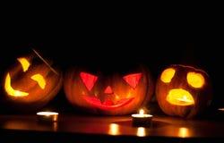 在黑背景的可怕万圣夜南瓜和瓜起重器o灯笼点燃了与小在周围和星蜡烛 免版税图库摄影
