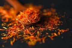 在黑背景的干番红花香料 未加工的有机雌蕊粉末番红花在桌上驱散 在木头的红色番红花香料 免版税库存图片