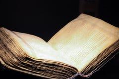 在黑背景的开放旧书 免版税库存照片