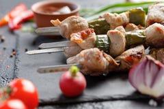 在黑背景的开胃静物画 从猪肉的烤肉串与新鲜蔬菜 库存图片