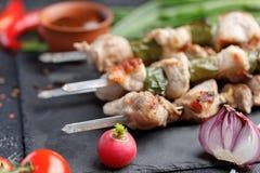 在黑背景的开胃静物画 猪肉烤肉串烹调了开火和新鲜蔬菜 免版税图库摄影