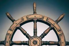 在黑背景的操纵的手轮船 免版税库存照片