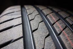 在黑背景的新的轮胎踩 库存图片