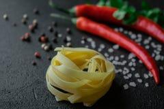 在黑背景的未加工的意大利细面条酱与辣椒新鲜的香菜枝杈海盐和干胡椒 图库摄影