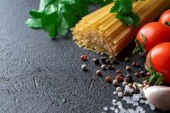 在黑背景的未加工的意粉用蕃茄、香料和粗糙的海盐 免版税库存照片