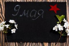 在黑背景的樱花5月9日, 红色星形 胜利的标志 荣誉5月9日 库存图片