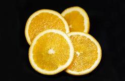 在黑背景的水多的橙色slieces 库存图片