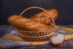 在黑背景的法国面包在篮子 库存照片