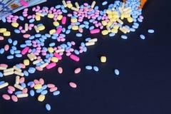 在黑背景的溢出的五颜六色的药片与文本间隔右下角 库存照片