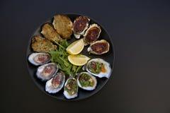 在黑背景的牡蛎盛肉盘 免版税库存图片
