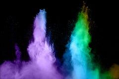 在黑背景的蓝色和紫色微尘爆炸 免版税库存照片