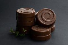 在黑背景的被堆积的巧克力漩涡饼干 免版税库存图片