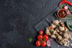 在黑背景的诱人的烤肉串 与新鲜蔬菜和调味汁的开胃肉 在您的文本下的地方 免版税库存照片
