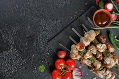 在黑背景的诱人的烤肉串 与新鲜蔬菜和调味汁的开胃肉 库存图片