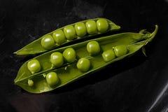 在黑背景的豌豆 免版税库存图片