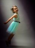 在黑背景的逗人喜爱的女孩跳舞 免版税库存照片