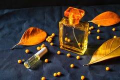 在黑背景的香水瓶和金香水 免版税库存图片