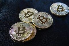在黑背景的Bitcoin Bitcoins金子在黑暗的桌上的颜色谎言 免版税图库摄影