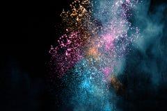 在黑背景隔绝的多彩多姿的粉末飞溅云彩 免版税库存图片