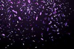 在黑背景隔绝的落的发光的闪烁紫色五彩纸屑 圣诞节或新年快乐五彩纸屑 免版税库存照片