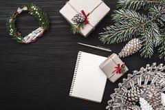 在黑背景,与锥体,装饰对象的一棵杉树 圣诞节礼物和一个笔记本,或者假日消息的 免版税库存图片