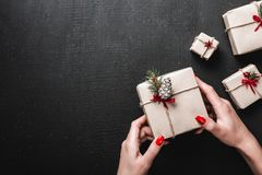 在黑背景,夫人拿着一件华美的礼物 手工制造礼物和Xmas大气 免版税库存照片