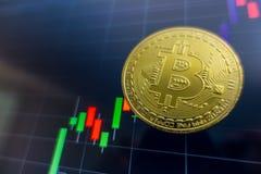 在黑膝上型计算机屏幕上的金黄Bitcoin有证券交易所图表的 免版税库存图片