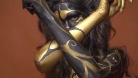 在黑色和金人体艺术的苗条妇女模型拉扯她的在照相机摆在前面的手 影视素材