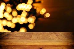在黑色和金子闪烁前面的空的桌点燃背景 对产品显示蒙太奇 库存图片