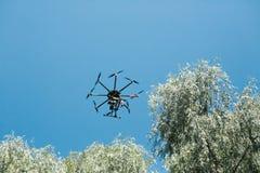 在黑色的无人航空器,飞行与一台数字照相机 有高分辨率一台数字照相机的邪魔  飞行 免版税库存照片