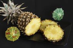 在黑色的盘子的切的成熟和黄色鸡尾酒,在黑暗的背景的伞的菠萝和装饰 免版税图库摄影
