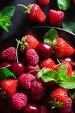 在黑色的盘子的新鲜的红色成熟莓果 免版税库存照片