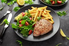 在黑色的盘子的油煎的金枪鱼排有新绿色、蕃茄沙拉、柠檬和炸薯条的 食物健康海运 免版税库存照片