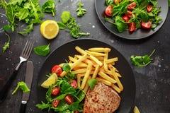 在黑色的盘子的油煎的金枪鱼排有新绿色、蕃茄沙拉、柠檬和炸薯条的 食物健康海运 免版税库存图片