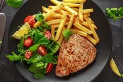 在黑色的盘子的油煎的金枪鱼排有新绿色、蕃茄沙拉、柠檬和炸薯条的 食物健康海运 免版税图库摄影
