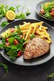 在黑色的盘子的油煎的金枪鱼排有新绿色、蕃茄沙拉、柠檬和炸薯条的 食物健康海运 库存照片