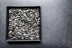 在黑色的盘子的烤向日葵黑背景表面01上 免版税库存图片