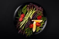 在黑色的盘子,黄瓜,蕃茄,有气味的草本,柠檬,莴苣的食物素食沙拉离开 菜单的好想法 库存图片