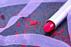 在黑色的红色唇膏与装饰对象 免版税库存图片