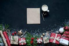 在黑色背景圣诞节装饰,箱子,树,盖帽,圣诞老人,星分支的圣诞节构成  库存图片