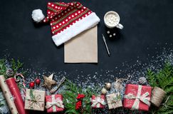 在黑色背景圣诞节装饰,箱子,树,盖帽,圣诞老人,星分支的圣诞节构成  免版税库存照片