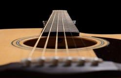 在黑色背景的声学吉他 免版税库存照片
