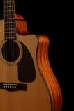 在黑色背景的声学吉他 库存照片