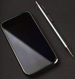 在黑色背景的Smartphone和笔 免版税库存图片