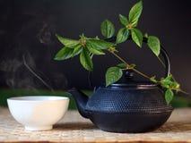 在黑色茶壶和空白杯子的亚洲热茶在席子 免版税库存照片