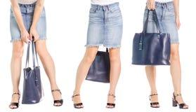 在黑色鞋子牛仔布的集合女性腿在手中避开经典手袋 免版税库存照片