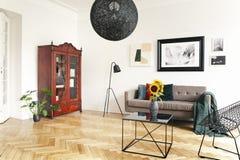 在黑色,大理石咖啡桌和被构筑的艺术上的黄色向日葵在典雅的客厅内部的高白色墙壁上 库存图片