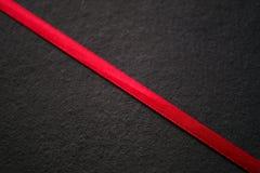 在黑色,纹理的红色丝带 库存图片