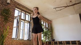 在黑芭蕾舞短裙的跳芭蕾舞者使灵活在跃迁 黑体和裙子的迷人的亭亭玉立的女孩执行一个跃迁从 影视素材