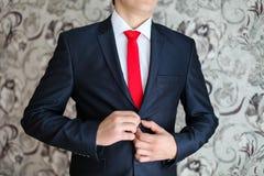 在黑衣服和一条红色领带的商人 巧妙的偶然成套装备 准备好的人工作 夹克的新郎,新郎紧固他的 库存照片